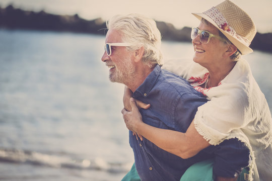 happy senior couple have fun and enjoy outdoor leisure activity at the beach. the man carry the woman on his back to enjoy together a retired lifestyle at the beach