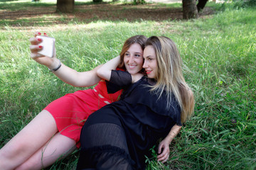 Girls smile and take a selfie together. Two girls stretched out in the grass take a selfie together and smile. In the background the green in the outdoor park.