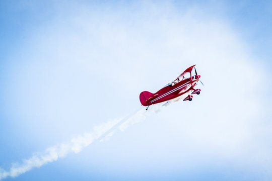 Red airplane with propellers and white smoke