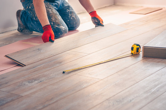 Working with hands installs a laminate board, professional flooring installation