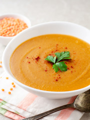 Red lentil cream soup on gray stone background