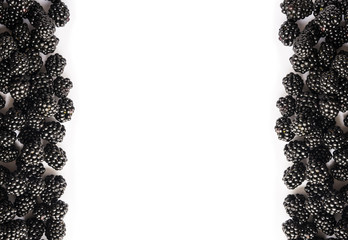 Top view. Ripe blackberries on white background. Berries at border of image with copy space for text.