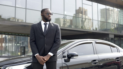 Confident Afro-American driver standing by car, security guard service, business