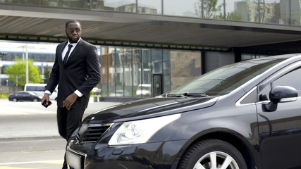 Confident African American man in business suit coming to his luxury automobile