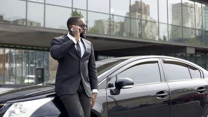 Serious rich man in expensive business suit talking over phone in big city
