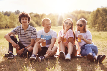 Positive two boys and girls have fun outside, enjoy unforgettable day together, sit on green grass, drink cold beverages, wear casual t shirts and shades, have happy expressions. Best companions