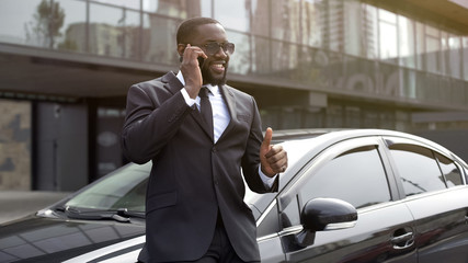 African American showing thumbs-up speaking on phone, manager concluded bargain