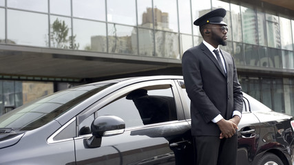 Driver of vip hotel service waiting for passengers near his car, ready to go