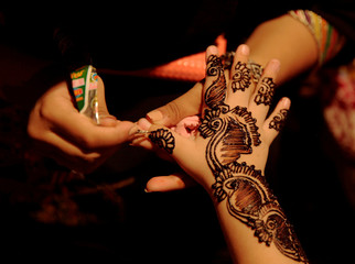 A girl applies mehndi on the hand of a customer at a stall ahead of Eid al-Fitr, which marks the end of the holy month of Ramadan