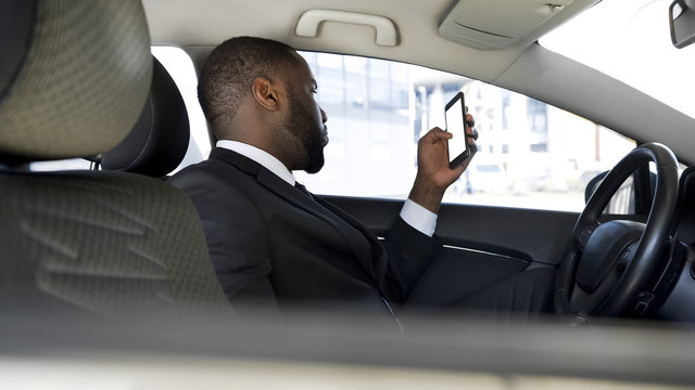 Man stuck in traffic jam, bored scrolling news application on his smartphone