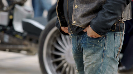 Man with hands in pockets of ripped jeans standing next to motorcycle, biker