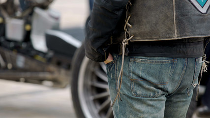 Tough biker with hands in jeans pockets standing next to his cool motorcycle