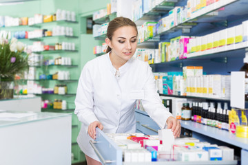 Woman pharmacist is looking different medicines in apothecary