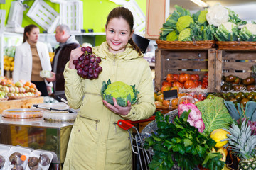 Preteen girl choosing ripe fruits and vegetables in greengrocery