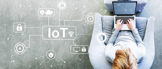 IoT Security theme with man using a laptop in a modern gray chair