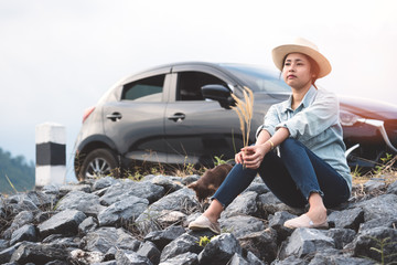 Young asian woman sitting with chihuahua dogs beside the road with black hatchback eco car. Stylish attractive girl traveler wear denim shirt traveling with pets in summer vacation. Lifestyle outdoor