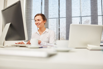 Junge Frau arbeitet online am Computer