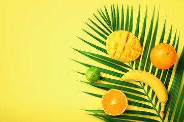 Fresh orange, banana, pineapple, mango smoothie and juicy fruits on palm leaves over yellow background. Detox summer drink. Vegetarian concept. Top view, flat lay, copy space