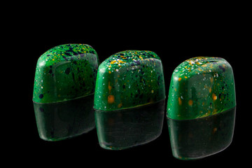 Luxury handmade chocolate candies on black background. Green candies with multicolored drops. Product concept for chocolatier