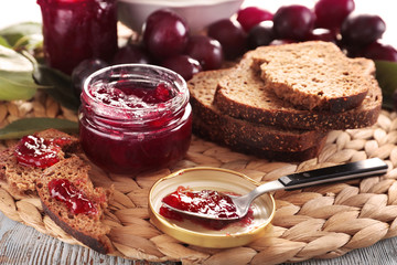 Tasty plum jam and bread on wicker mat