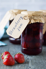 Strawberry jam in glass jars and fresh strawberries on a gray background.