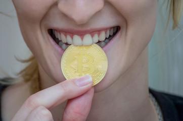 Man bites a gold coin with his teeth. Bitcoin