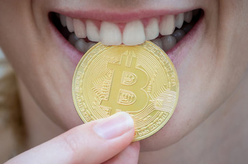 Man bites a gold coin with his teeth. Bitcoin