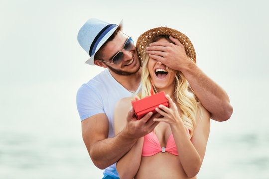 Young man suprising his girlfriend with gift on the beach