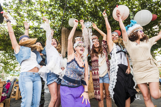 group of crazy women mixed ages from young to old having fun and dancing all together in a hippy style event. celebrating group people concept with clored clothes and happiness