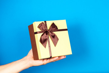 Human hand holding brown ribbon wrapped holiday surprise gift or present box package on blue background