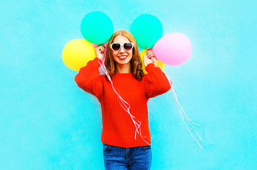 Cool stylish girl holds a colorful air balloons on blue background