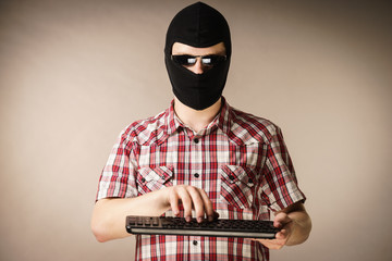 Man wearing balaclava holding keyboard