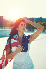 Young woman covered USA flag daydreaming outdoors