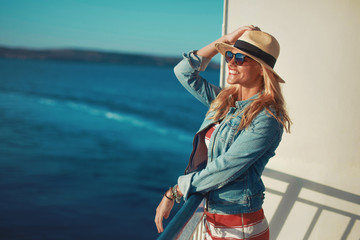Young blonde woman traveler posing on cruise ship deck