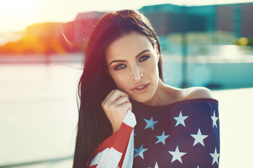 Sexy brunette woman covered in USA flag portrait in sunset