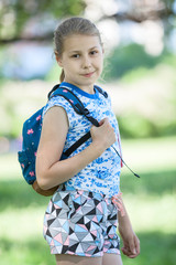 Portrait of ten year old girl with small backpack on her back, summer garden