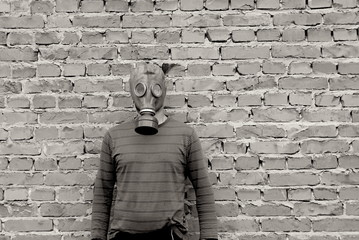 A man in a gas mask against a brick wall is black and white
