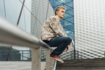 Young man with floral pattern shirt on a cityscape.