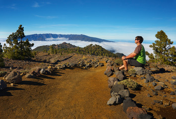 Resting man watching a landscape with the volcanic crater Caldera de Taburiente on background, Island of La Palma, Canary Islands, Spain