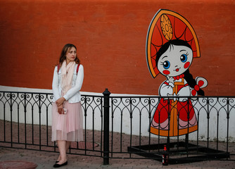 A woman stands near a cutout of a Russian cartoon character in central Moscow