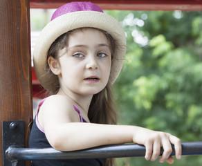 Summer portrait of a little girl in a straw hat