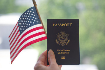 Passport of USA and American Flag in hand. Blurred background.