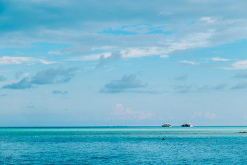 Maldives background. Sunset over the tropical sea and coral beach with colorful clouds in the sky. Boats on the horizon in heavenly atoll of peace and relaxation.