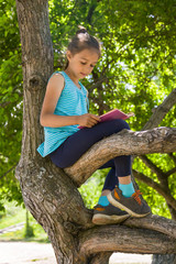 Cute little girl is sitting on a tree in summer park and reading a book