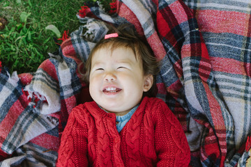 Happy baby lying on plaid blanket and laughing