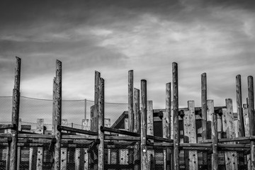 abstract design from big wooden columns against the background of the cloudy storm sky of monochrome tone