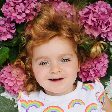 Pretty portrait of a red-haired girl surrounded by Hydrangea flowers.