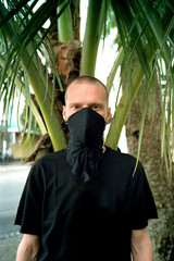 Man in protective mask on tropical background