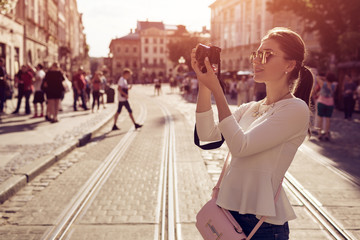 Happy young woman tourist takes picures in old city. Summer travel. Vacation and holidays concept