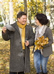 Middle-aged couple walks in the autumn forest.